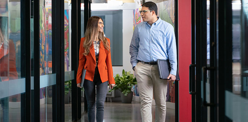 Man and woman walking in office hallway talking
