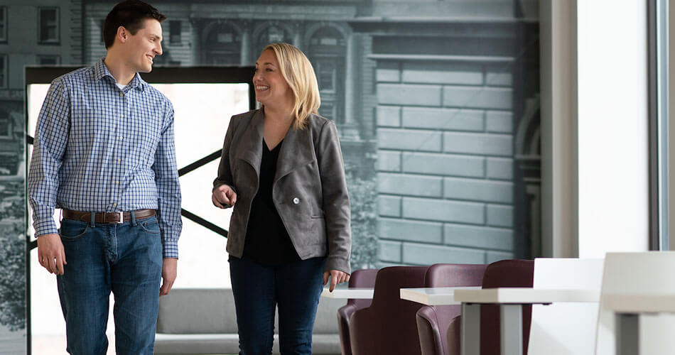 Man and woman walking together down office hallway and talking
