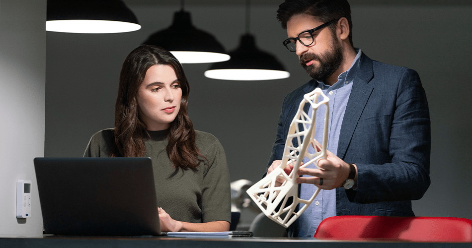 Man showing 3D printed part to woman at laptop computer