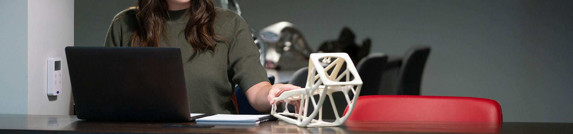 女子在电脑前触摸3D打印零件