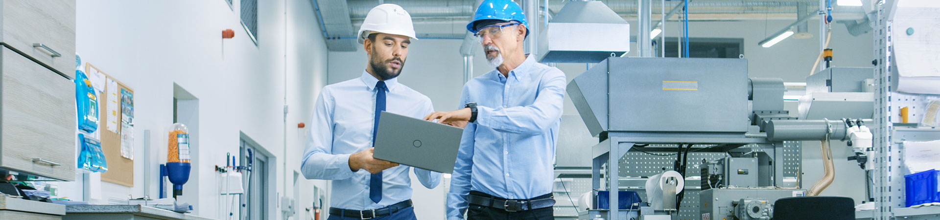 Two men on factory floor looking at laptop
