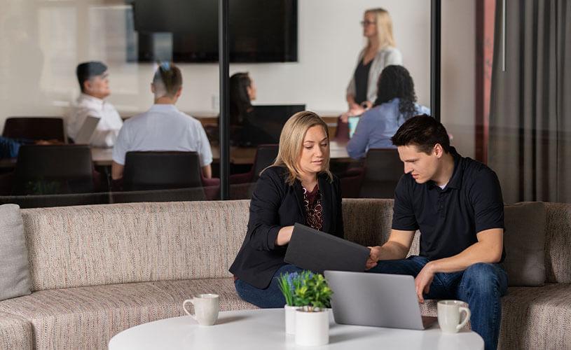 一男一女指着平板电脑屏幕,背景是一群人